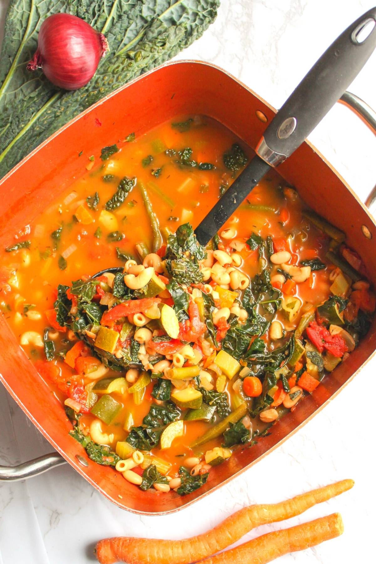 Vegan minestrone soup in a large soup pan with a ladle.