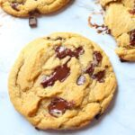 Eggless chocolate chip cookies cooling on a counter