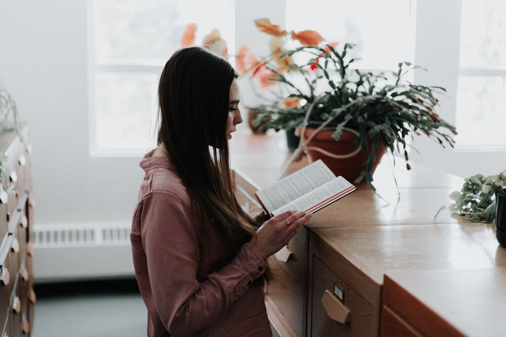 Woman standing in a a brightly lit room reading a book.