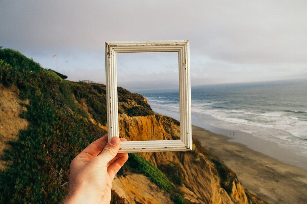 Person holding a picture frame on a mountain
