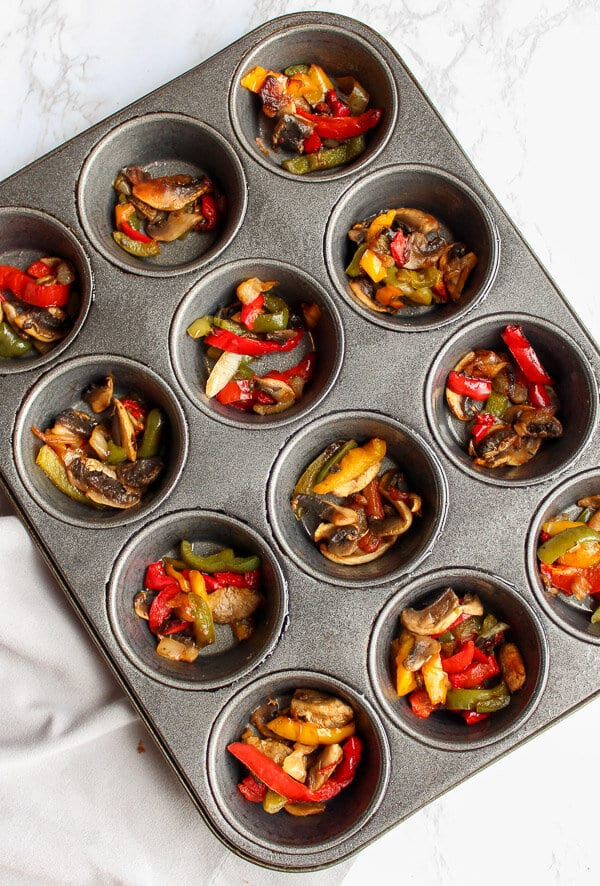 Muffin tin filled with sauted bell peppers