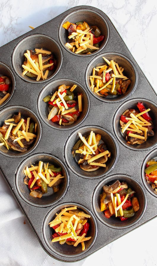 Muffin tin filled with cooked bell peppers and vegan cheese