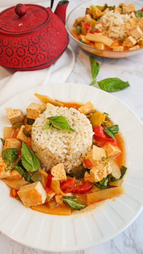 Vegan Thai red curry with tofu in a bowl topped with fresh basil