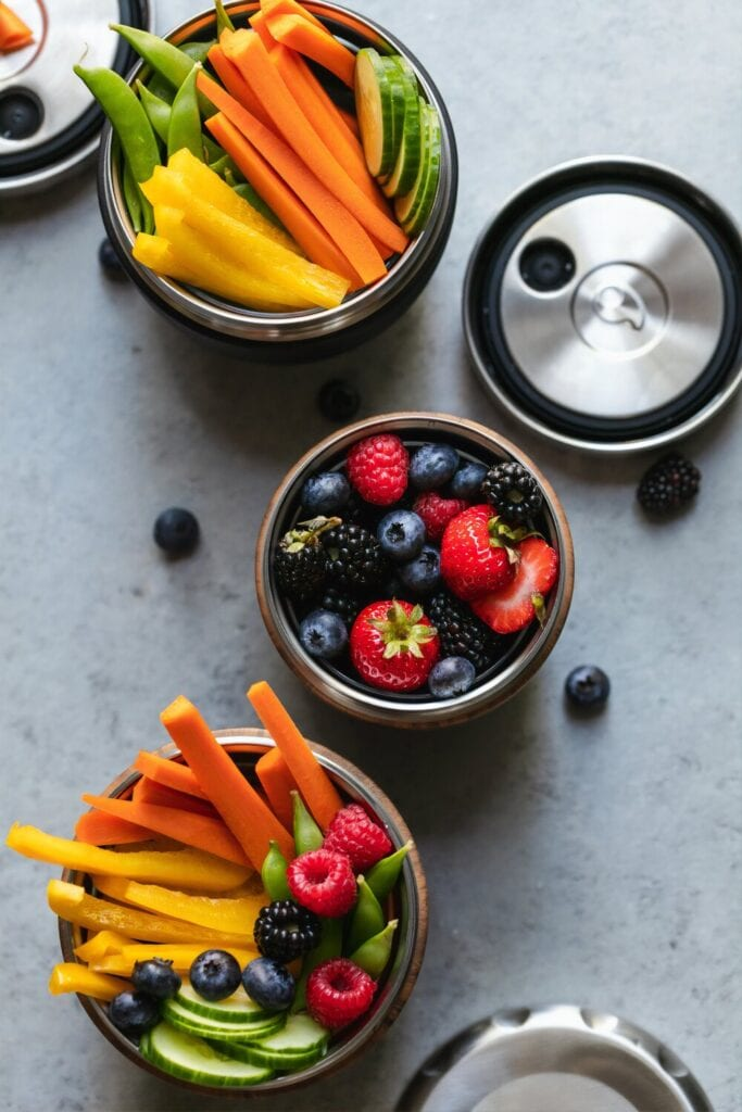 cut up peppers, vegetables and fresh berries in bowls