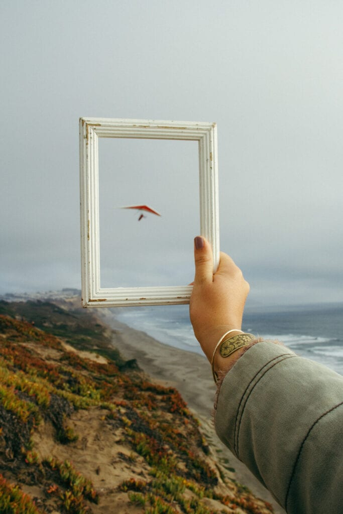 Hand holding a picture frame outside