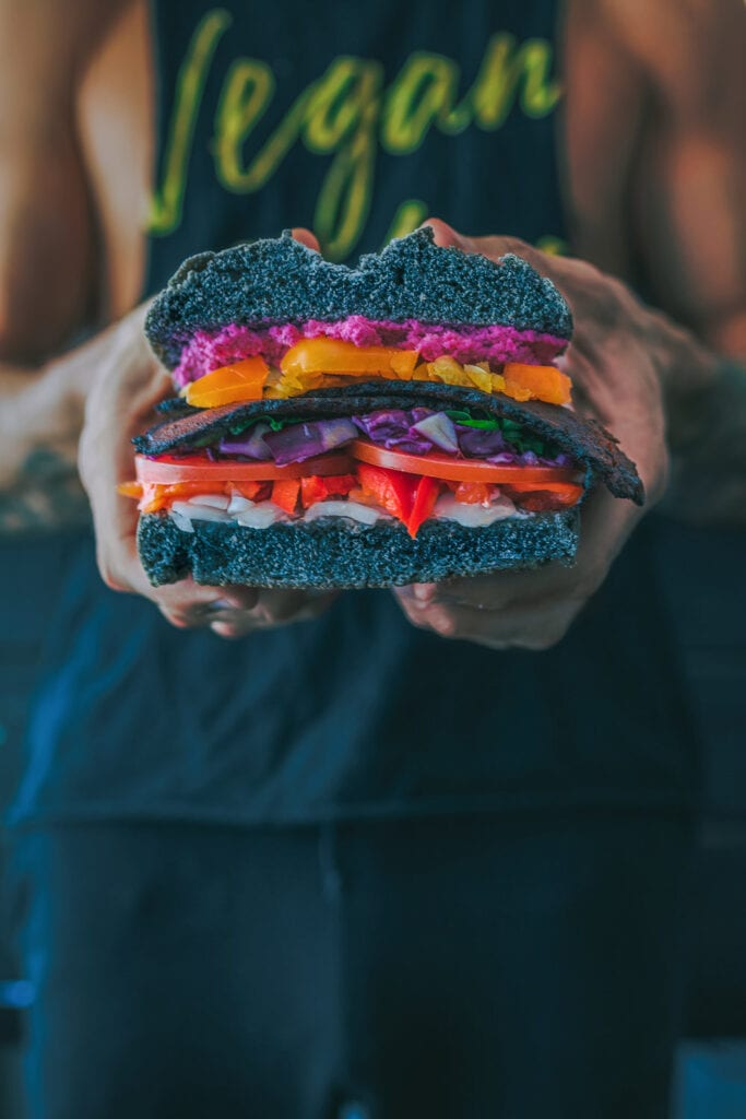hand holding a colorful and large veggie sandwich