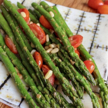 air fried asparagus on a plate with cherry tomatoes