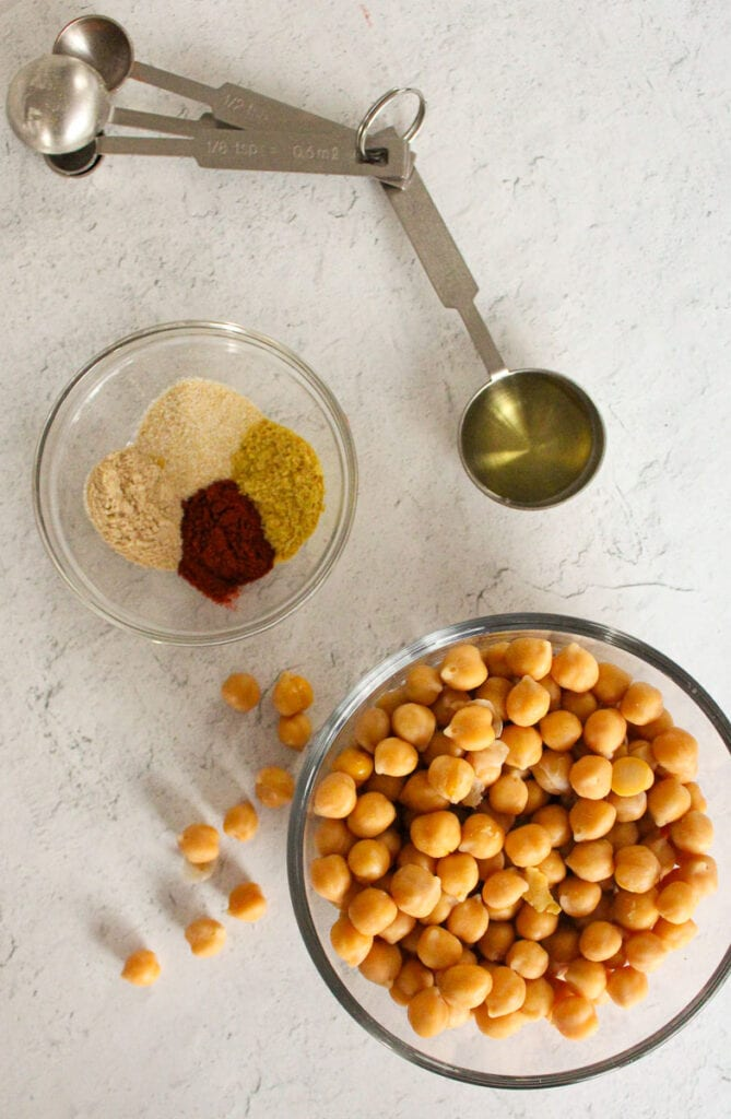 Crispy chickpea ingredients in individual bowls: chickpeas seasonings and oil.