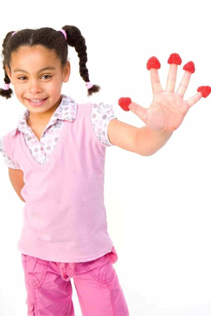 little girl smiling while holding up hand with raspberries on fingers.