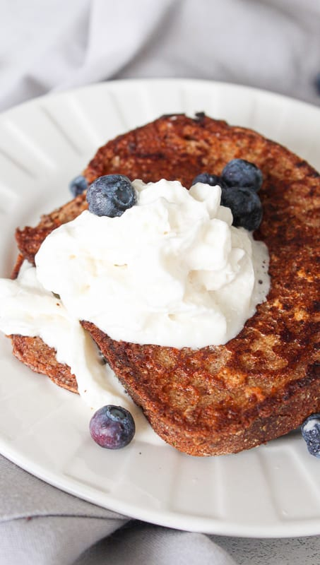 Vegan french toast with syrup, whipped cream and blueberries