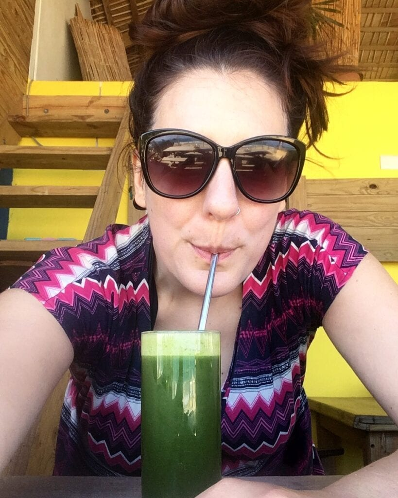 Woman with sunglasses sipping a green juice with a straw.