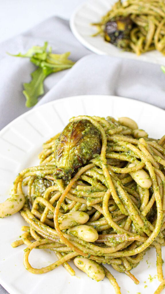 Pesto pasta on a white plate with roasted brussels sprouts