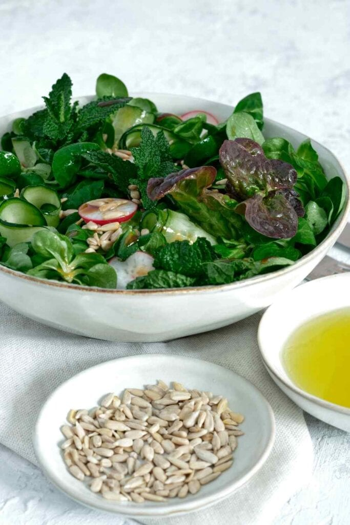 Side green salad with vinaigrette and a small bowl of sunflower seeds.
