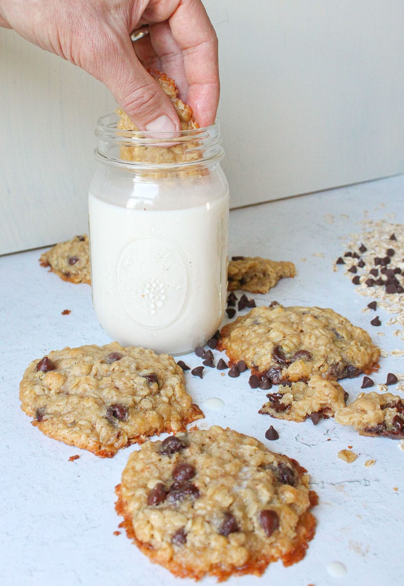 Hand dunking vegan oatmeal chocolate chip cookies into a mason jar of soy milk