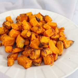 Sweet potatoes cubed and roasted and sitting on on a white plate