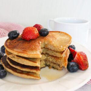 Stack of vegan pancakes with fresh berries and maple syrup.