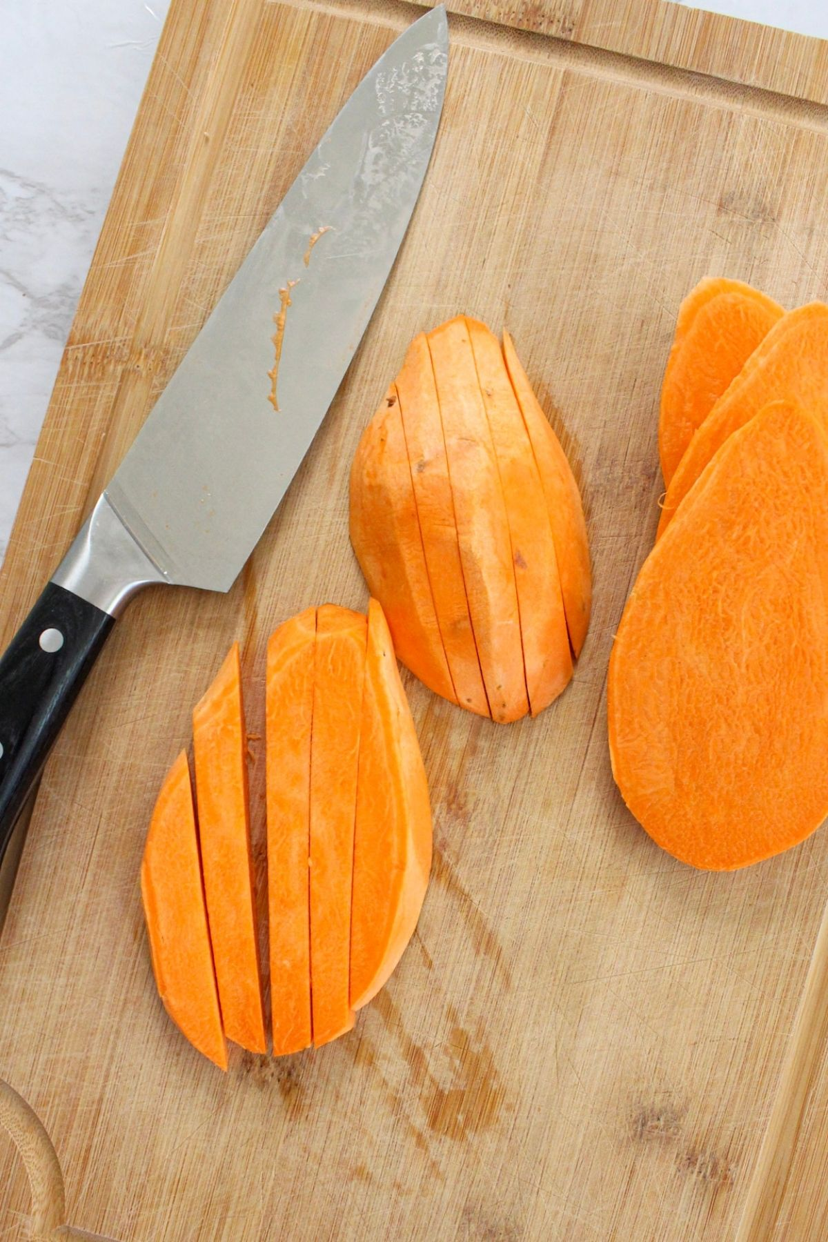 Sweet potatoes peeled and on a cutting board.