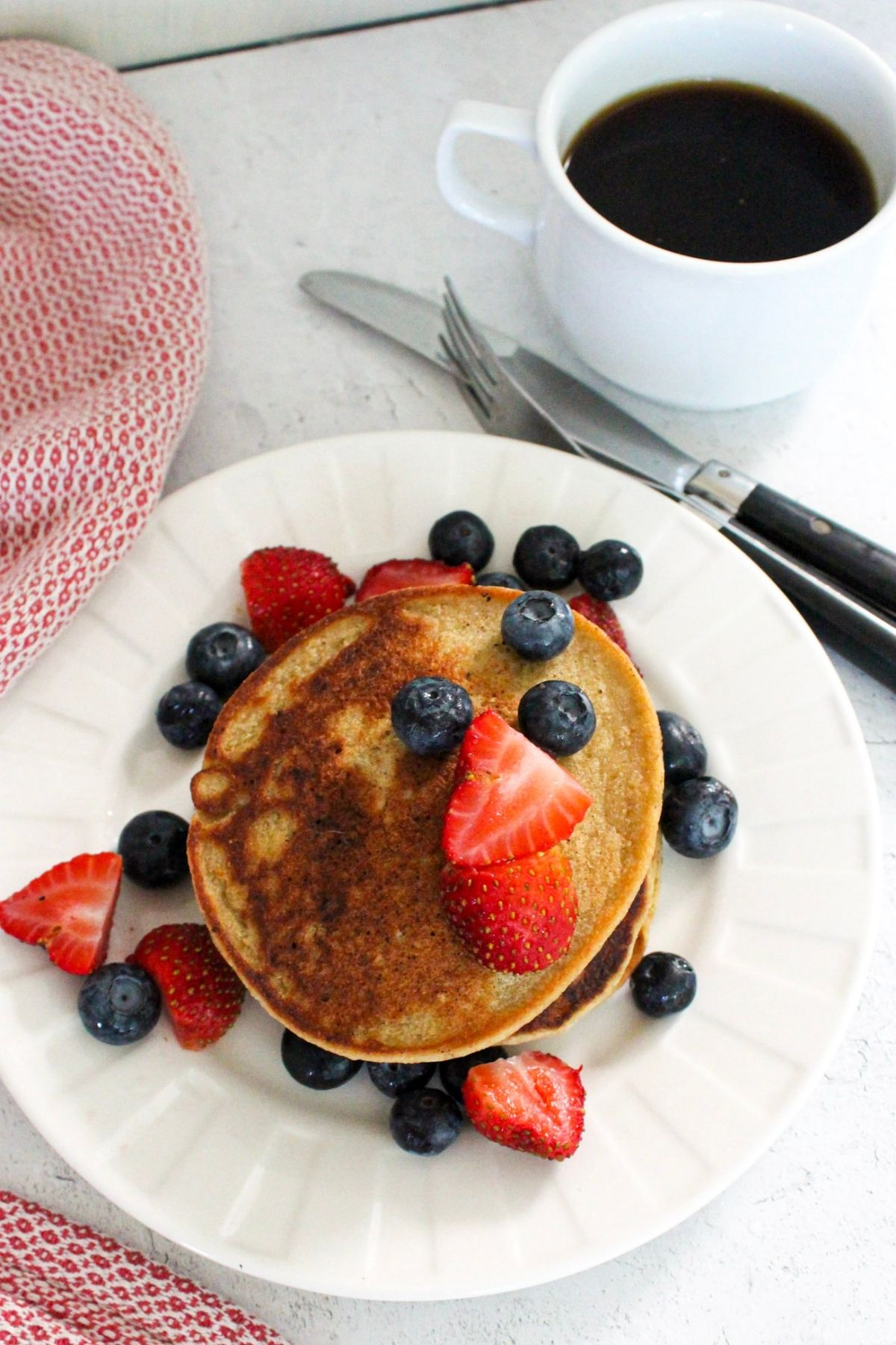 Vegan oatmeal banana pancakes topped with fresh fruit on a table with coffee.