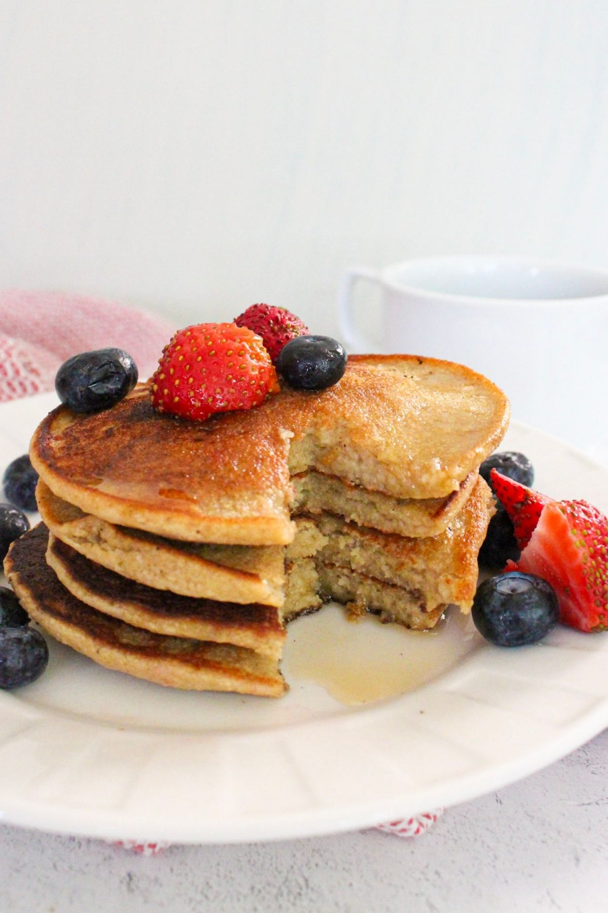 Stack of vegan oatmeal banana pancakes on a plate with fresh berries