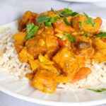 Close up of vegan butter chicken and rice on a plate.