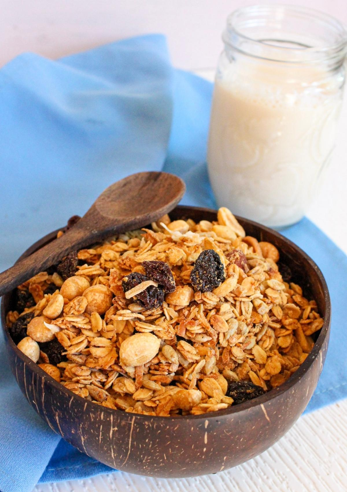 Vegan granola in a bowl with a wooden spoon and glass of milk