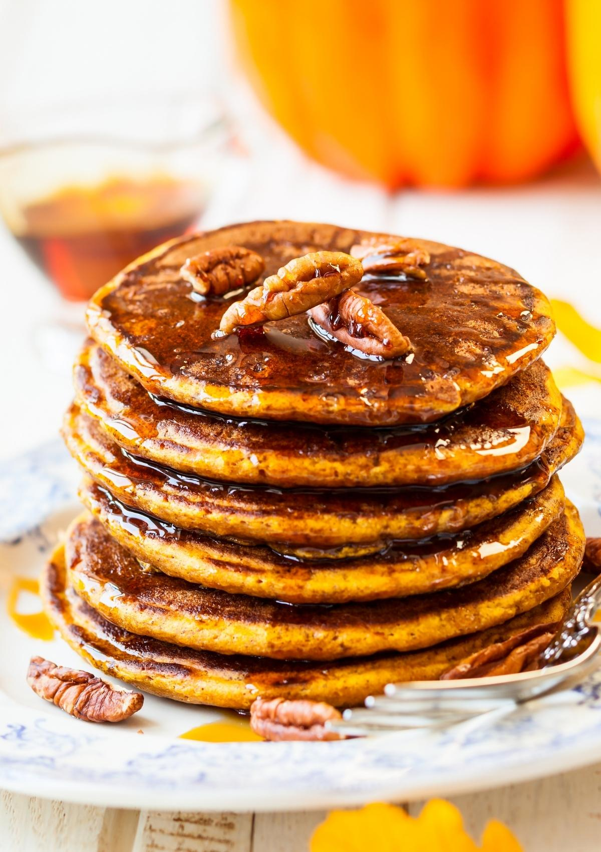 A stack of vegan pumpkin pancakes topped with maple syrup