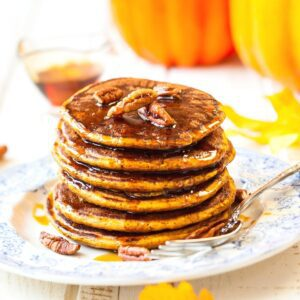 A stack of vegan pumpkin pancakes on a plate dripping with maple syrup